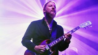 a shot of derek trucks on stage