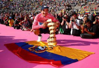2019 Giro d'Italia winner Richard Carapaz poses with Ecuador's flag on the final podium in Verona.