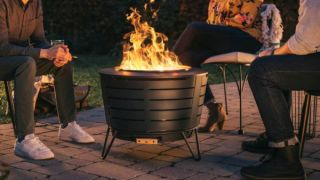 Best fire pits: Three adults sit around a large, stylish fire pit in the garden at night