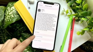 An iPhone showing the ios 15 update screen. The phone is resting on a notebook with pens, Airpods and plants surrounding it