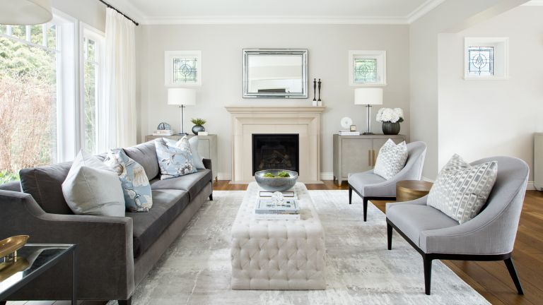 A neutral living room with white fireplace, gray sofa, and tall windows