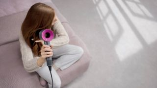 A woman drying her hair with a Dyson hair dryer