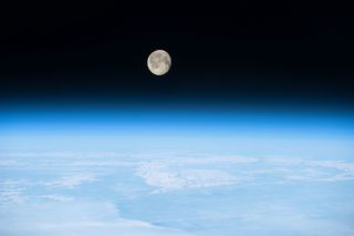 Photo of a nearly full Moon shining brightly on the Earth's atmosphere, taken from the International Space Station.