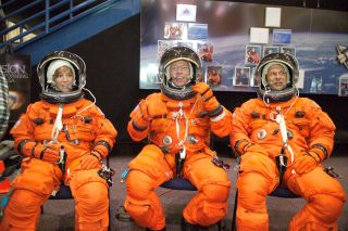 The astronauts Lisa M. Nowak, Michael E. Fossum and Piers J. Sellers wear training versions of the shuttle space suit.