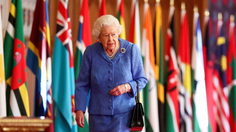 In this undated image released on March 6, 2021, Queen Elizabeth II walks past Commonwealth flags in St George's Hall at Windsor Castle, to mark Commonwealth Day, in Windsor, England.