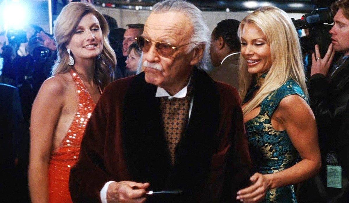Iron Man Stan Lee, dressed as Hugh Hefner, with two beautiful models