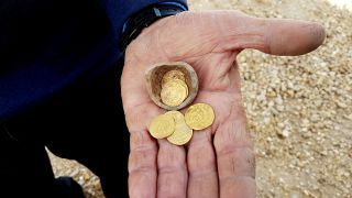 An archaeologist holds 7 gold coins and a sharp of the broken pot they were found in.