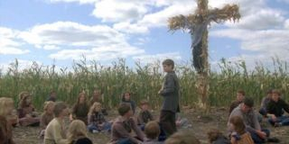 A group of children sit in the middle of a cornfield in a scene from 'Children of the Corn'