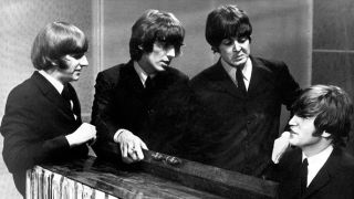 During the recording of a televised program in TV GRANADA studio in Manchester, the four members of the British pop group the BEATLES talking next to the piano, 1962-1965.