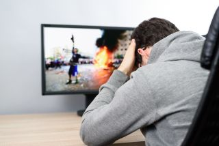 troubled man watching (on TV) news about civil riots, aggressive protesters