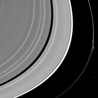 Saturn's rings reach across the photo, and the outermost, thin one