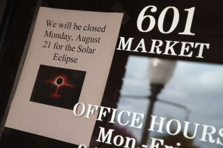 A sign in the window of a business in Metropolis, Illinois, tells visitors they will be closed on August 31 for the solar eclipse.