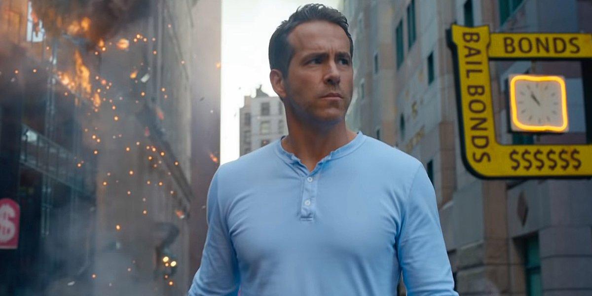 Ryan Reynolds walking through streets of destruction in Free Guy.