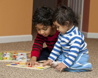A brother and a sister play with puzzles pieces.