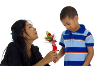 A boy apologizes to his mother with flowers.