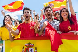 People cheering on Spain for a sports game.