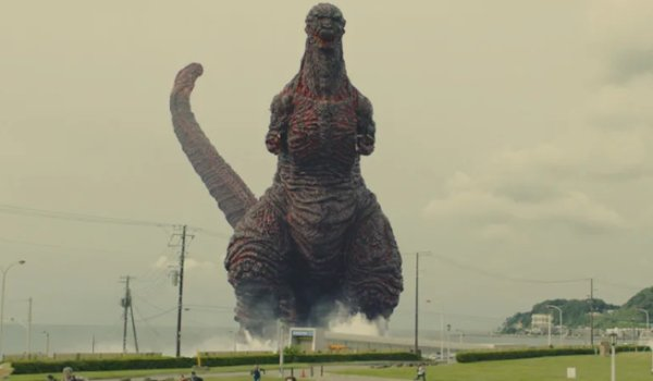 Shin Godzilla the monster towers over land, walking out of the water