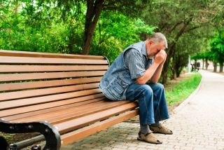 An older man sits on a park bench, looking very sad.