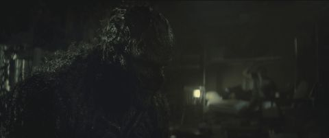 Swamp Thing looms over the shadow of Avery Sunderland in a wooden cabin