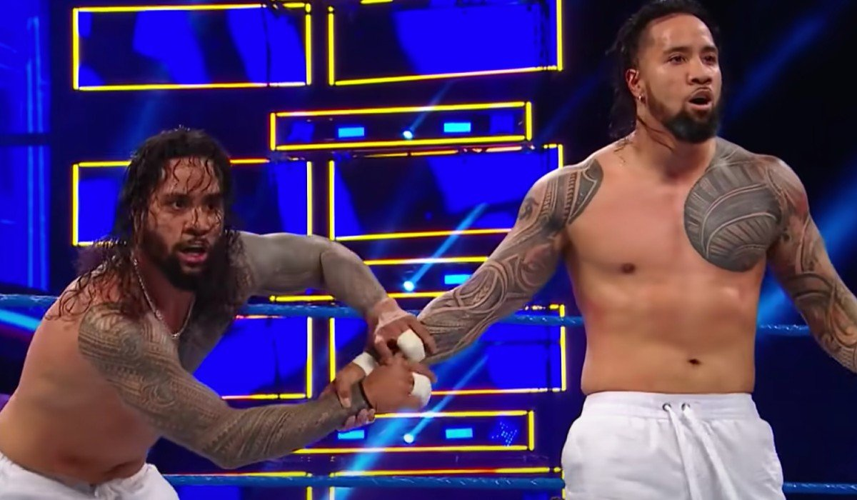 Jey and Jimmy Uso getting ready to jump over the top rope WWE