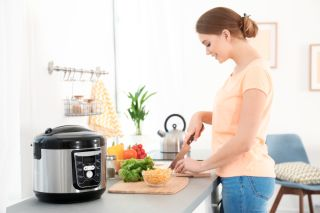 woman cooking in kitchen with pressure cooker