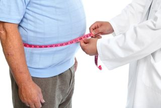An overweight man getting his waist size measured by a doctor.