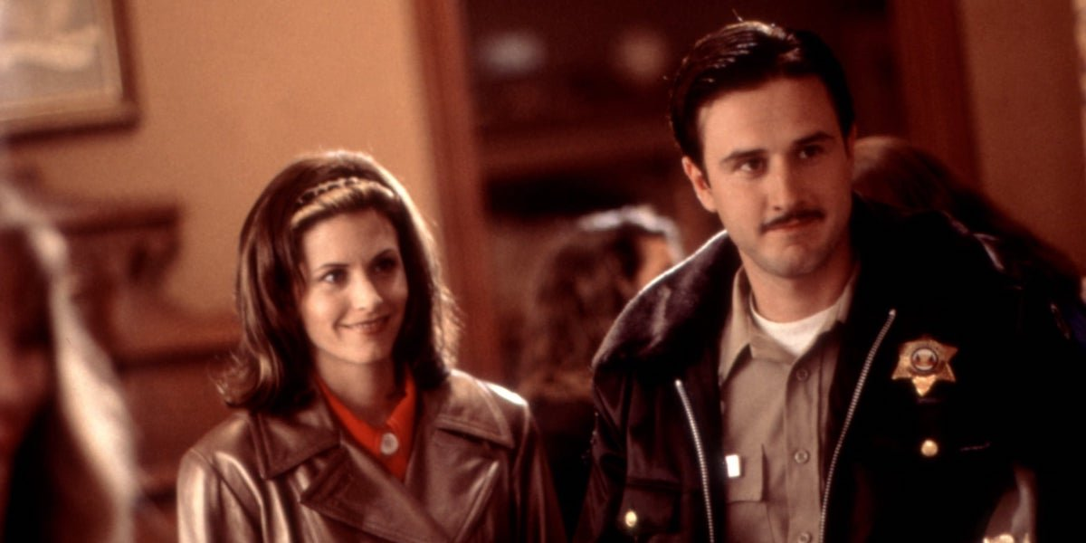Gale Weathers (Courtney Cox) and Dewey Riley (David Arquette) stand together and smile in 'Scream'