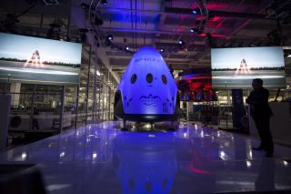 SpaceX CEO and Chief Designer Elon Musk (right) unveils the Dragon V2 manned spacecraft on May 29, 2014 during an event at the company's Hawthorne, California rocket factory.
