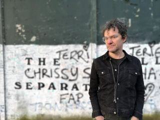 Mark Cousins in front of a graffiti-sprayed wall