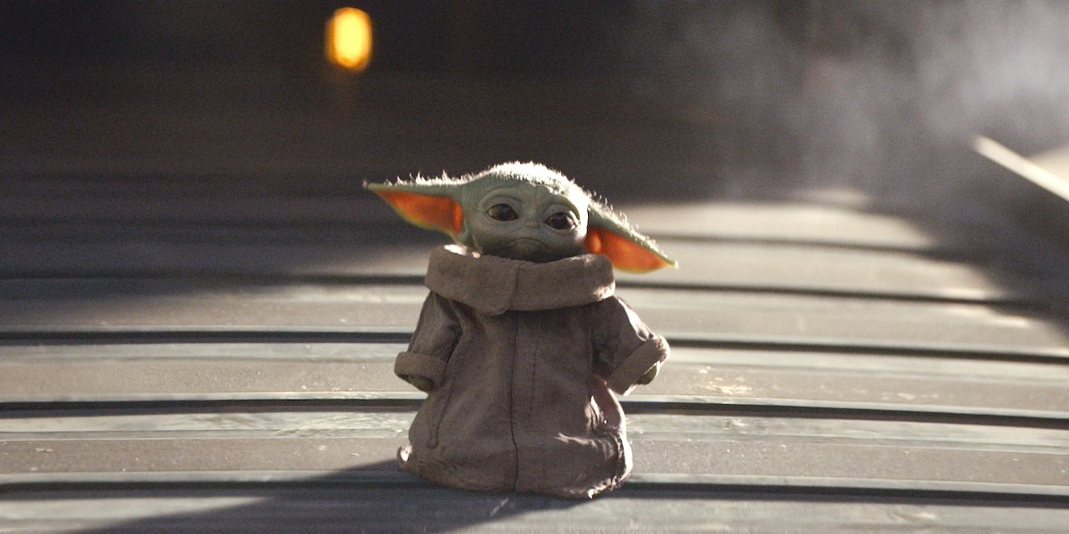 Baby Yoda standing by himself looking sad.