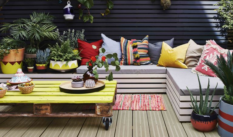 colourful painted seating area on a decked patio with a yellow pallet coffee table and colourful outdoor cushions