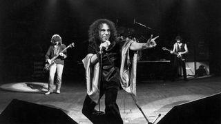 Photo of Ronnie DIO and BLACK SABBATH; L-R - Geezer Butler, Ronnie Dio (doing devil horns - manu cornuta), Tony Iommi at Gaumont.