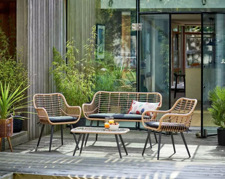 Argos garden furniture set, 4 seater bamboo sofa with cushions on a decking placed with large glass windows and doors