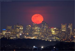 The full pink moon rises over Boston in this photo taken by Chris Cook on Wednesday (April 11). April's full moon isn't actually pink; it's named after the wild ground phlox, one of the first flowers to bloom in spring. Cook said the full moon appeared red-orange that evening due to the thick atmosphere, dust, haze and pollen in the air.