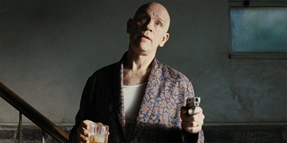 John Malkovich holding a drink and a gun in Burn After Reading