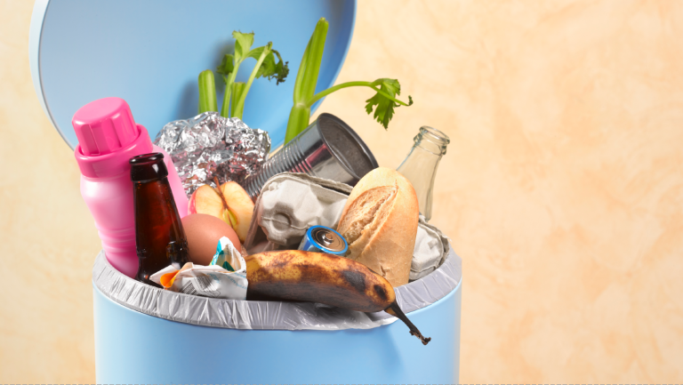 Trash bag with rotting food in dustbin - stock photo