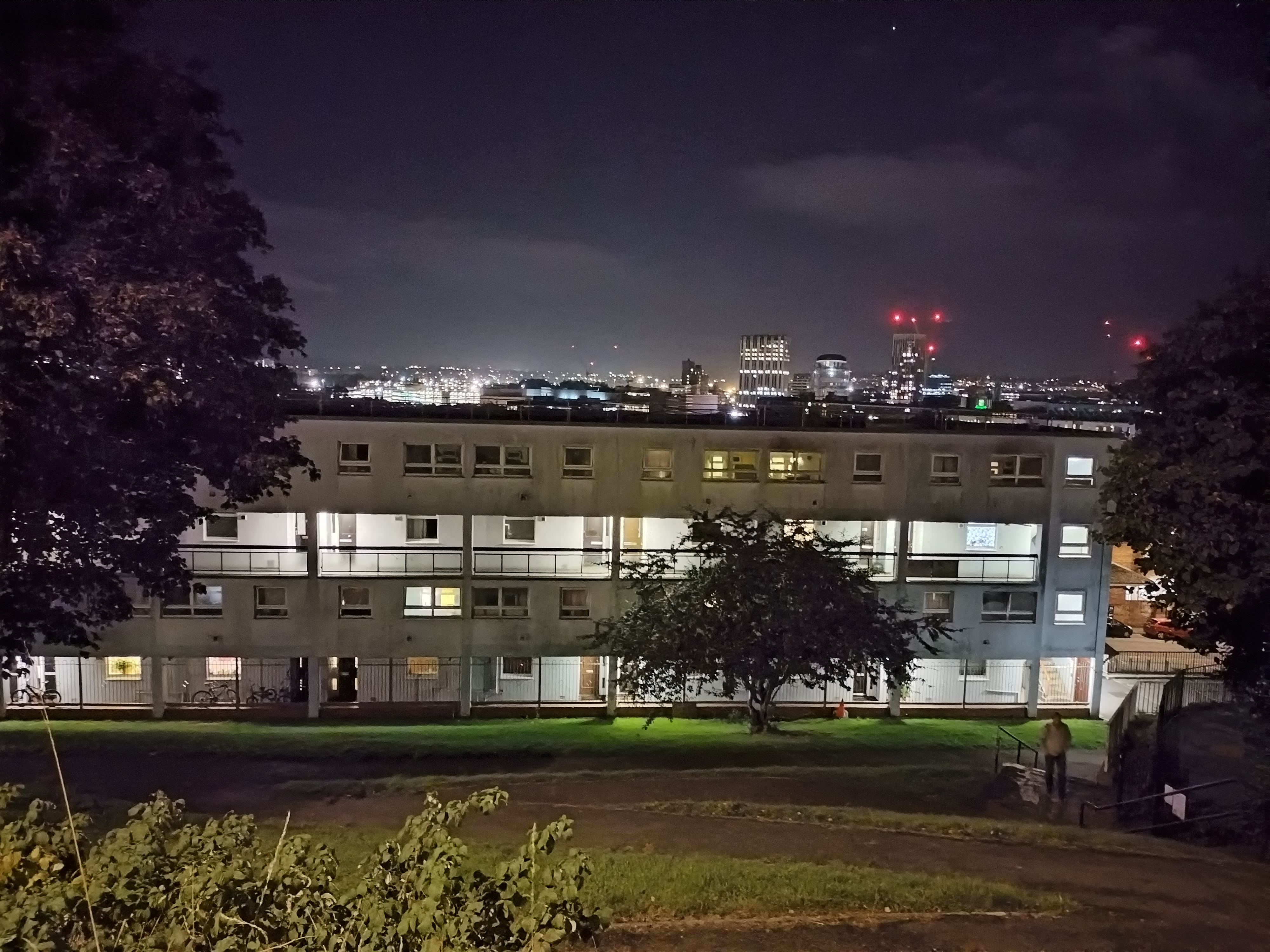 A photo of a block of flats at night
