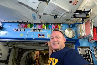 "A ""happy birthday"" sign hangs behind NASA's Butch Wilmore on the International Space Station."