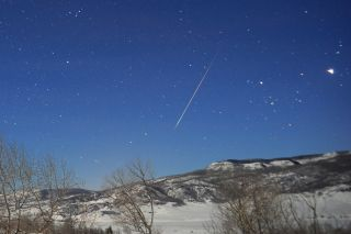 A meteor falls through the sky.
