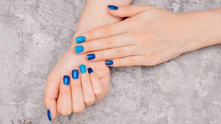 close up of manicured nails with shiny blue polish