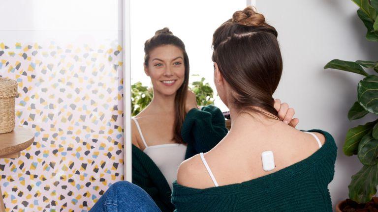 Person sat in front of mirror wearing the Upright Go 2 posture corrector