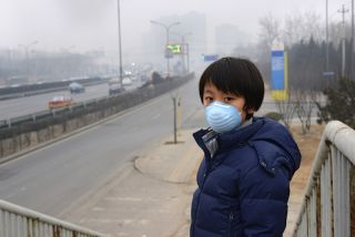 boy wearing a face mask in beijing against pollution