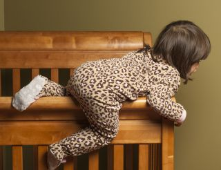 A toddler climbs out of her crib.