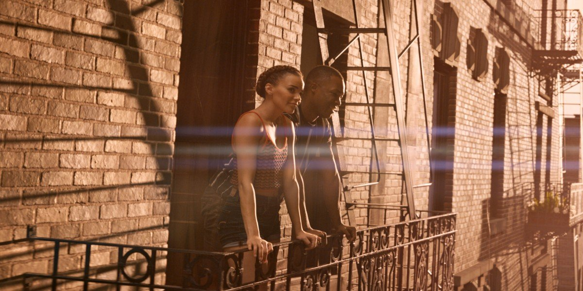 Leslie Grace and Corey Hawkins as Nina and Benny gazing at the sunset in In the Heights