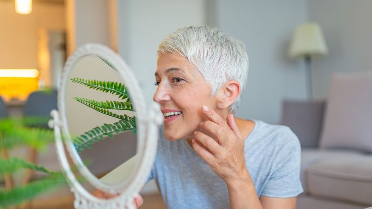How to lose weight from your face: woman looking in the mirror