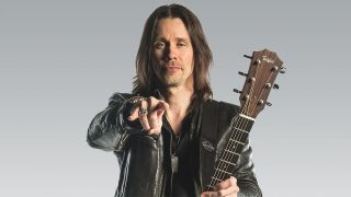 A photograph of Myles Kennedy holding a guitar and giving the devil horns
