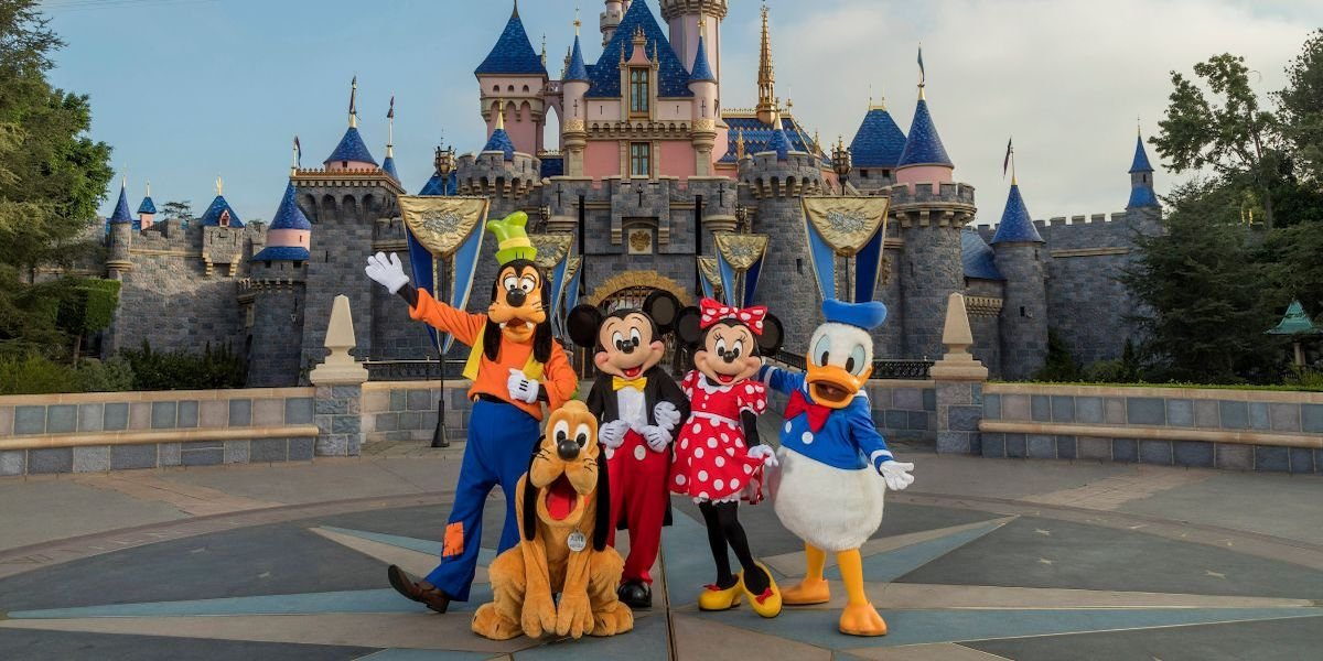 Goofy, Pluto, Mickey, Minnie and Donald Duck stand in front of Sleeping Beauty's Disneyland castle.