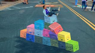 A woman sat on top of the milk crate challenge street art.