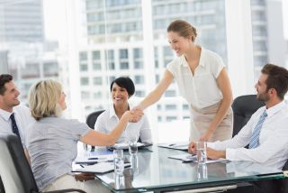Women shake hands at a business meeting.