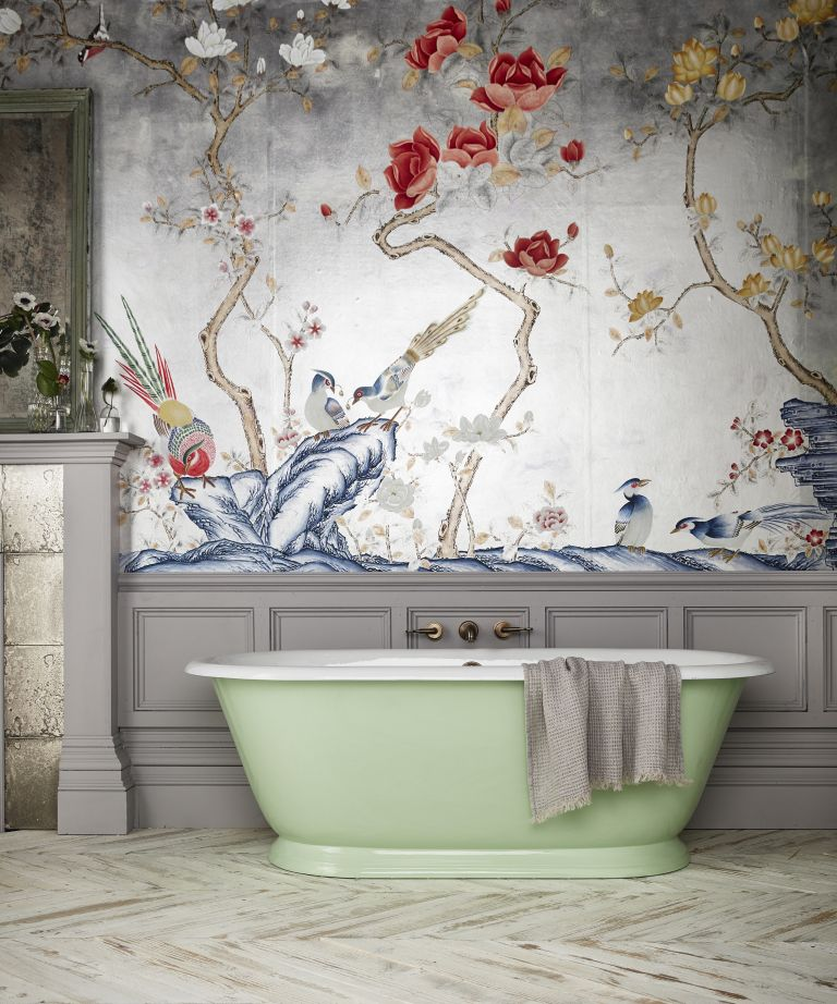 Glossy bathroom with large green bath tub and ornate paper